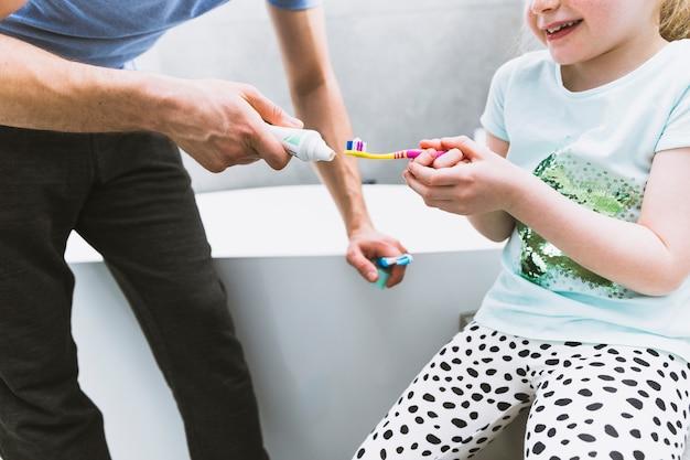 Père de la culture mettant dentifrice sur la brosse à dents de la fille