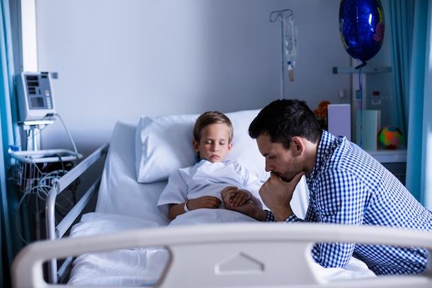 Père déprimé tenant la main de son fils