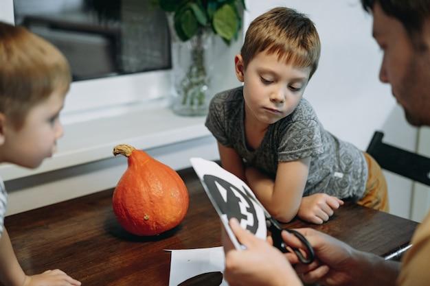 Père et deux enfants découpant un gabarit pour fabriquer une lanterne jack en citrouille orange. image avec mise au point sélective. photo de haute qualité