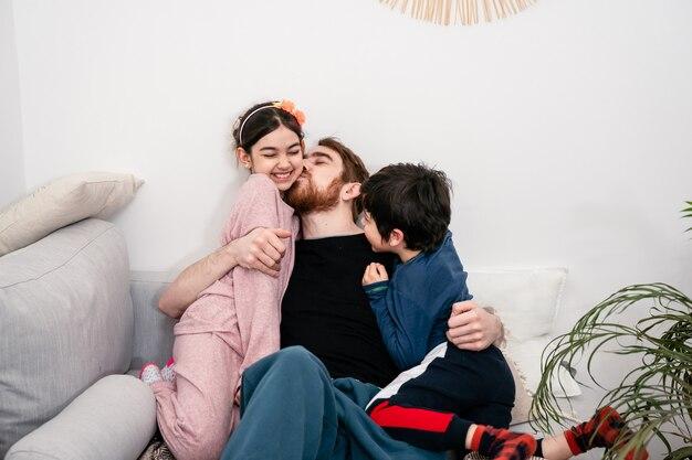 Père et deux enfants embrassant et s'amusant sur un canapé à la maison. famille multinationale. vraie vie, convivialité, diversité, confort à la maison
