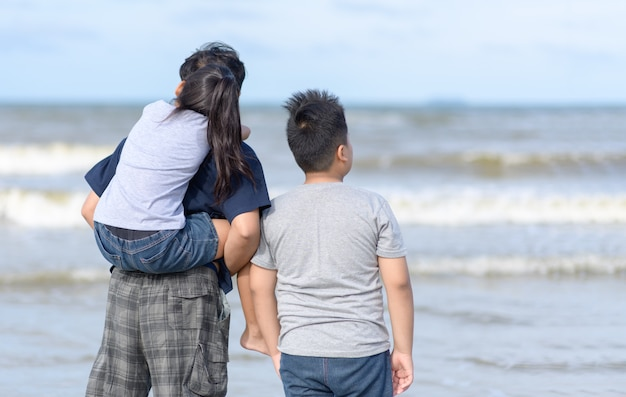 Père et deux enfants marchant sur la plage,