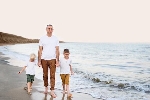 Père et deux fils marchent le long du littoral. profiter des vacances