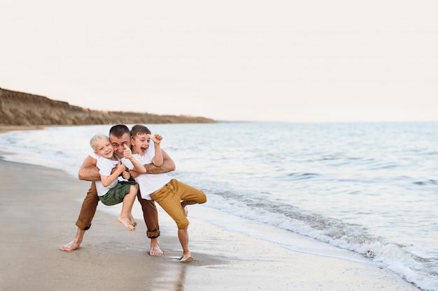 Père et deux fils montrent la classe, côte de la mer.
