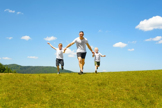 Père de deux jeunes enfants qui courent main dans la main sur le champ vert