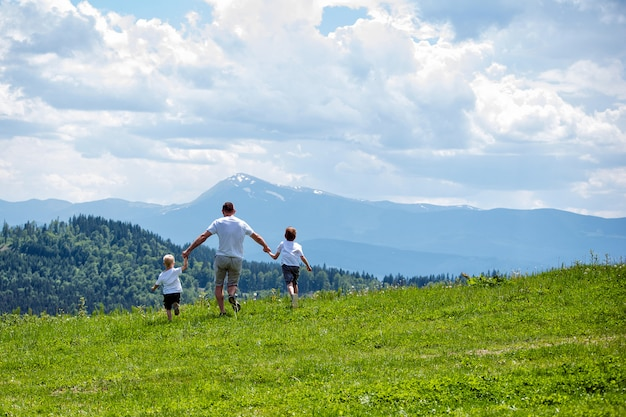 Père et deux jeunes fils courir sur le champ vert, main dans la main
