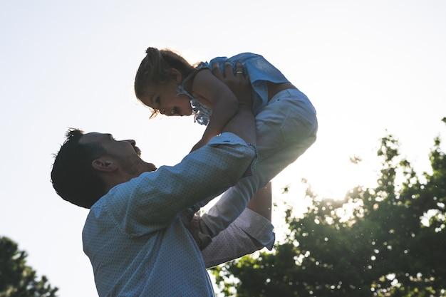 Père divorcé jouant avec sa fille à l'extérieur.