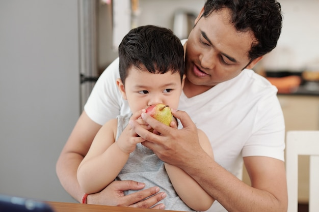 Père donnant une poire mûre sucrée à son petit fils affamé quand ils sont assis à table dans la cuisine
