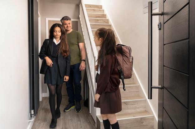 Père emmenant ses filles à l'école