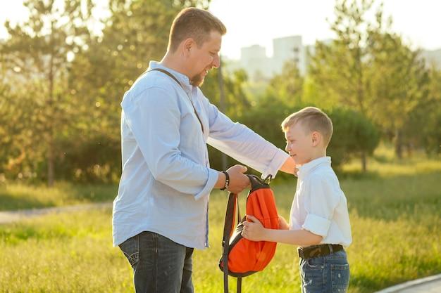 Le père emmène son fils à l'école. écolier élégant et jeune dans une chemise blanche et un jean avec un sac à dos dans le parc