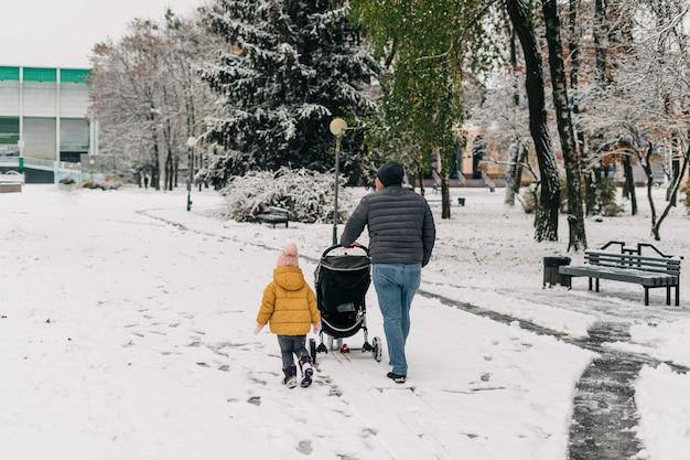 Père avec enfant et bébé marchant avec poussette dans le parc à neige d'hiver.