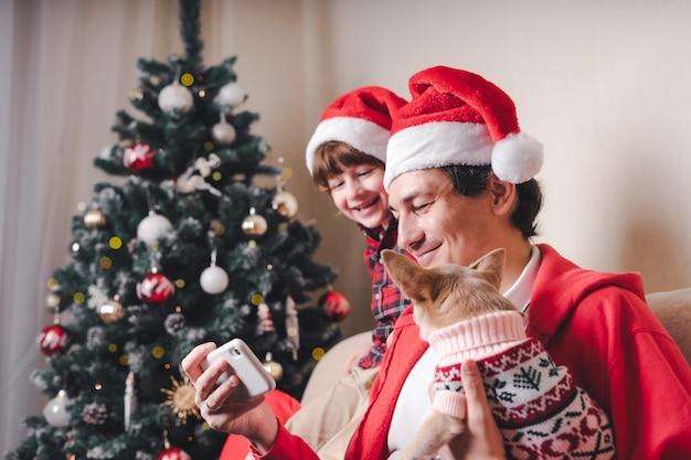 Père avec enfant et chien chiot en chapeaux santa holding cell phone