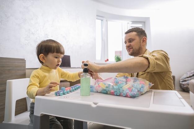 Père et enfant construisant des jouets de pièces lego