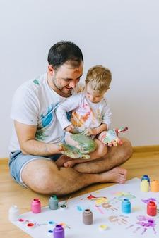 Père et enfant jouant avec des couleurs de peinture