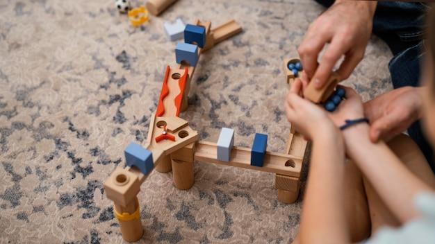 Père et enfant jouant avec des jouets vue élevée