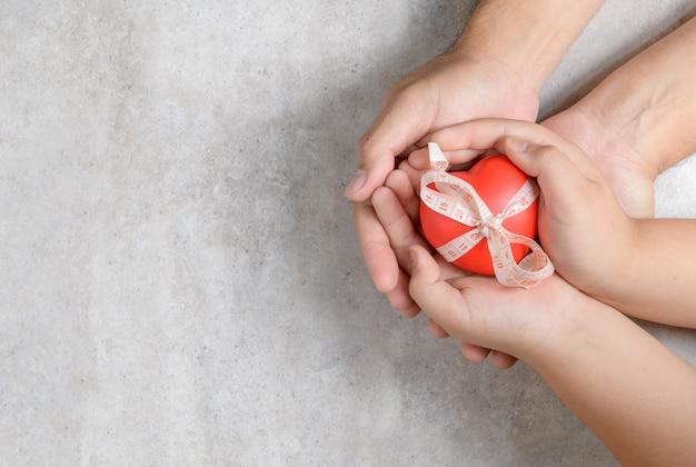 Père, enfant, mains, tenue, coeur rouge