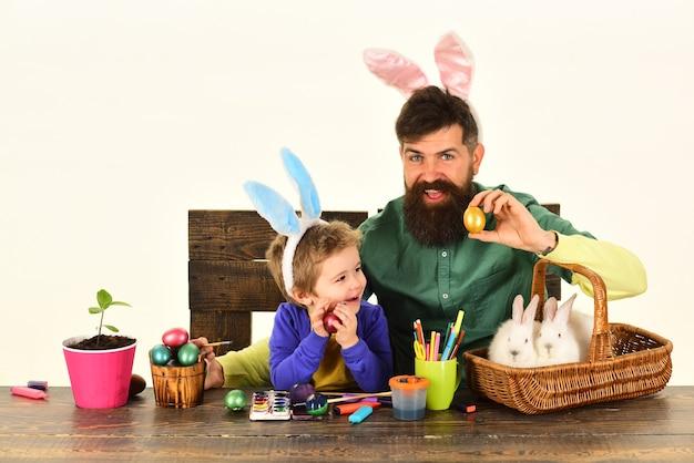 Père et enfant peignant des oeufs de pâques oreilles de lapin concept enfant tenant un panier avec des oeufs peints
