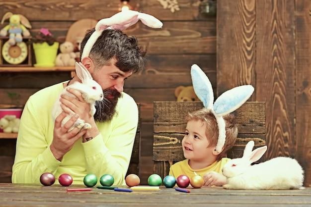 Père et enfant peignant des oeufs de pâques.