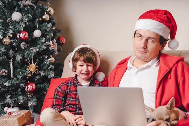 Père et enfant qui pleure avec un ordinateur portable à noël