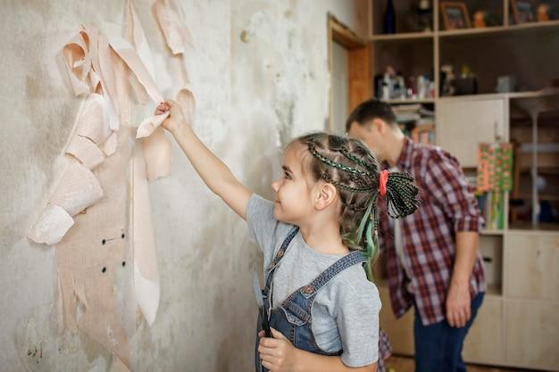 Père avec enfant réparant la pièce ensemble et papier peint immuable ensemble