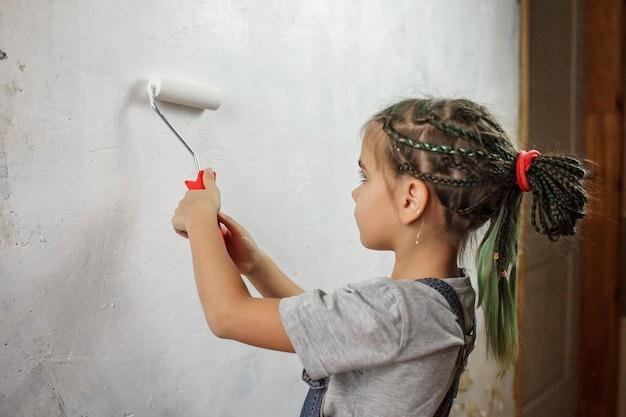 Père avec enfant réparant la pièce ensemble et peignant le mur ensemble