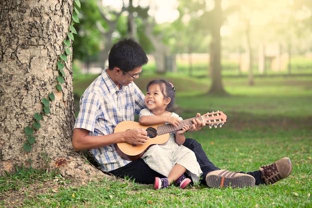 Père et enfant s'amuser à jouer de la guitare ensemble dans le parc