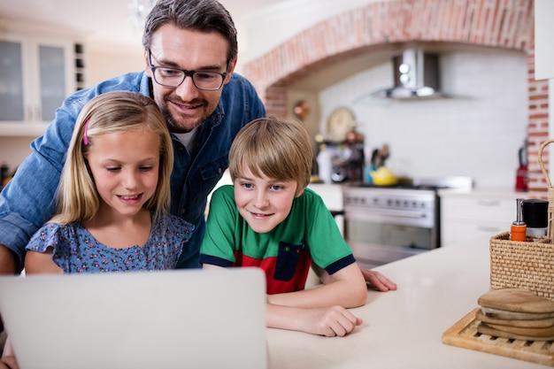 Père et enfants à l'aide d'un ordinateur portable dans la cuisine