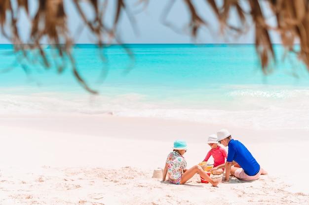Père et enfants faisant château de sable sur la plage tropicale. famille, jouer, plage, jouets