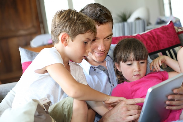 Père et enfants jouant avec une tablette à la maison