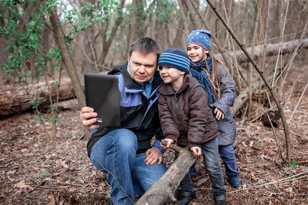 Père avec enfants marchant dans la forêt et se connectant avec la grand-mère pour montrer un rapport vidéo via en ligne