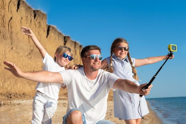Père avec enfants prenant selfie sur la plage pendant la journée.