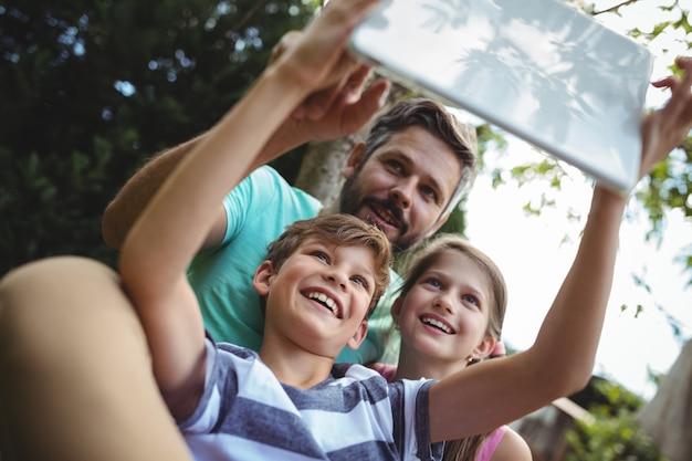 Père et enfants prenant un selfie avec tablette numérique