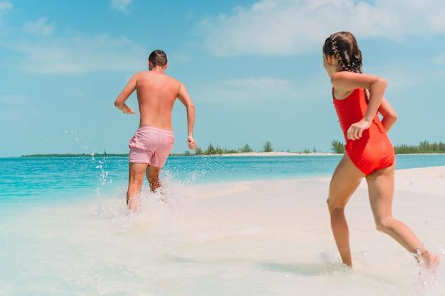 Père et enfants profitant des vacances d'été à la plage