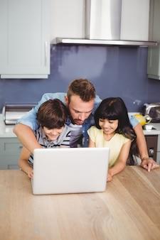 Père et enfants utilisant un ordinateur portable