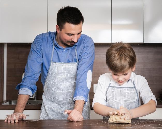 Père enseignant son fils à rouler la pâte