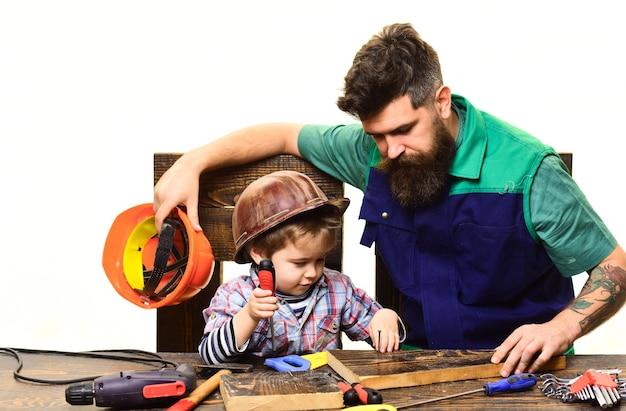 Le père enseigne au fils de réparer le cas du fils et du père qui répare ensemble un homme barbu avec une petite assistante