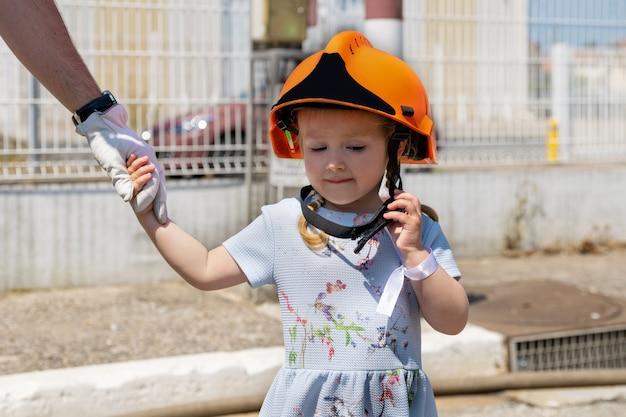 Le père enseigne à sa fille la formation de pompier en plein air