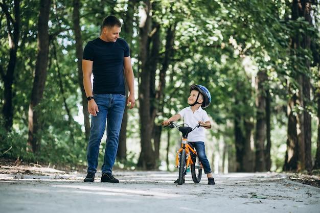 Père enseigne à son petit fils à faire du vélo