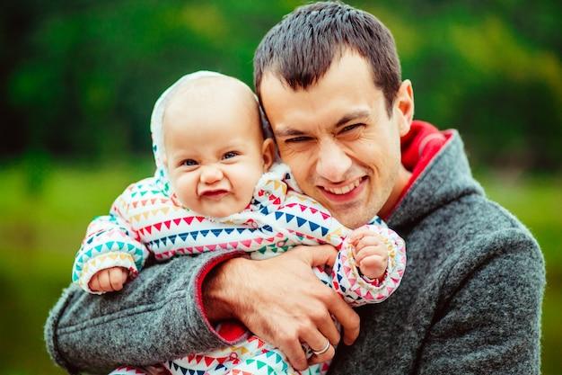 Père étreignant bébé dans le parc