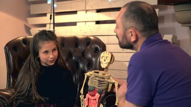 Père expliquant à sa fille cadette la structure osseuse du corps humain sur squelette