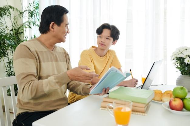 Père expliquant un sujet difficile à son fils adolescent qui fait ses devoirs pour l'école