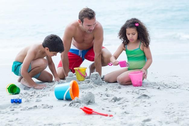Père faisant des châteaux de sable avec des enfants à la plage