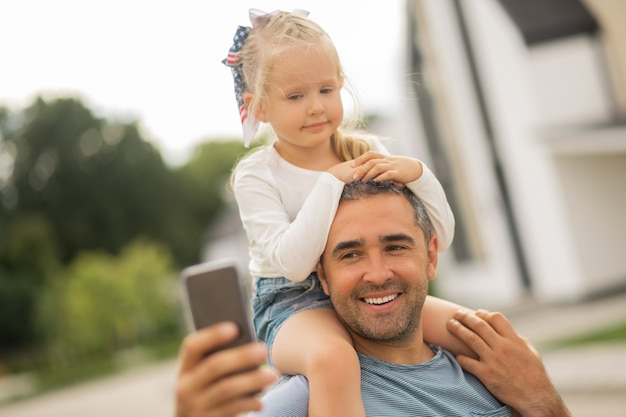 Père faisant selfie. jolie fille aux cheveux blonds regardant dans la caméra pendant que son père fait un selfie