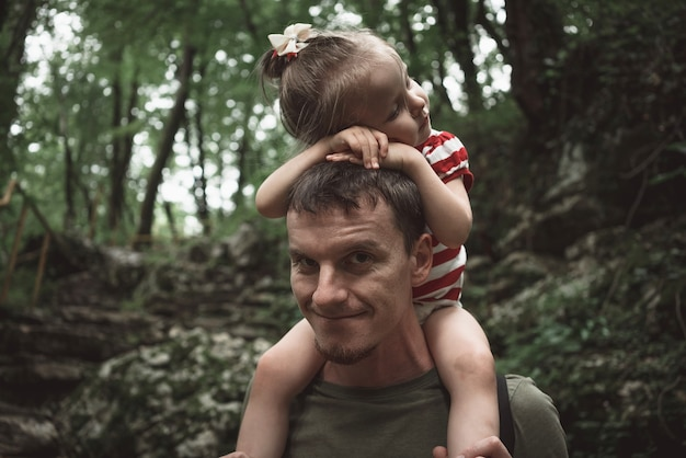 Père fatigué avec sa fille endormie sur le cou dans la forêt