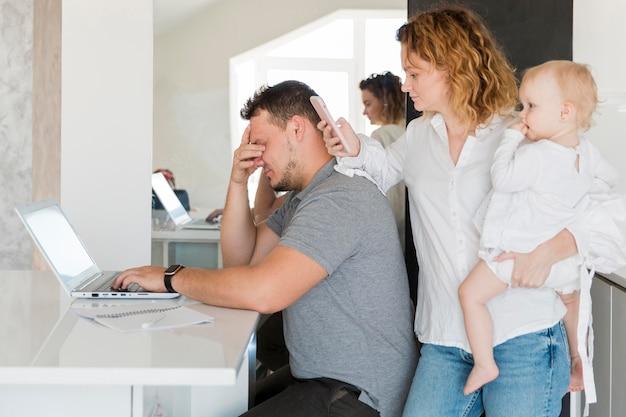 Père fatigué travaillant sur ordinateur portable