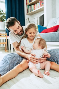 Père fier tenant sa petite fille nouveau-née à la maison