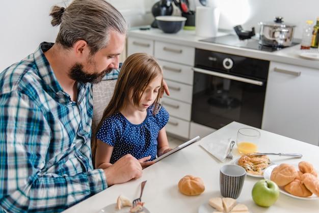 Père et fille à l'aide d'une tablette pendant le petit-déjeuner