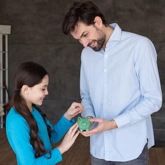 Père et fille à angle élevé avec tirelire