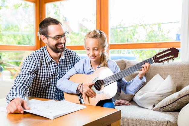 Père et fille apprenant à jouer de la guitare