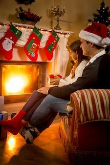 Père et fille assis sur une chaise à la cheminée décorée pour noël