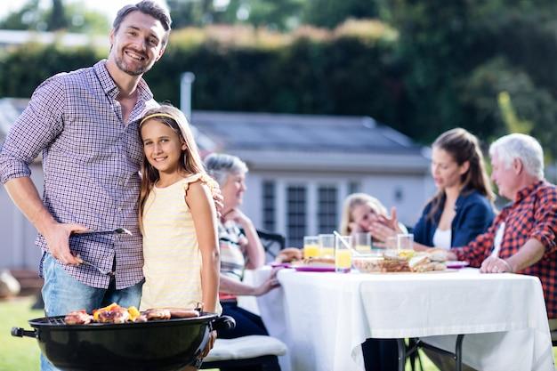Père et fille au barbecue pendant que la famille déjeune